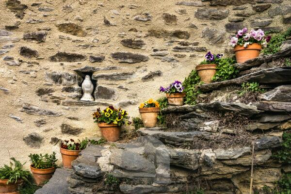 Stone stairs in Evol and flower pots in spring, Les Plus Beaux Villages de France,