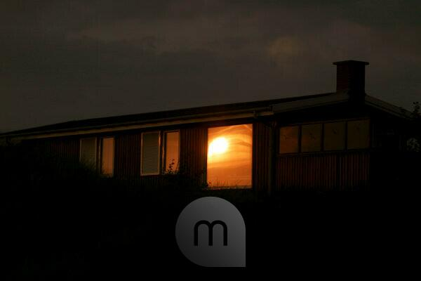 Summer house, evening, sun reflected in the window