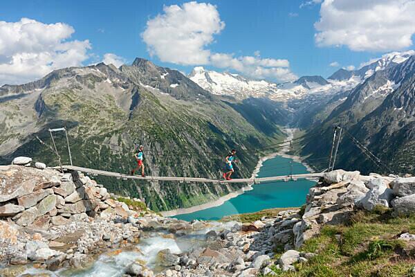 zwei Läufer auf der tibetanischen Brücke in der Nähe der Olpererhütte mit Schlegeis Stausee im Hintergrund, Zillertaler Alpen, Tirol, Bezirk Schwaz, Österreich.