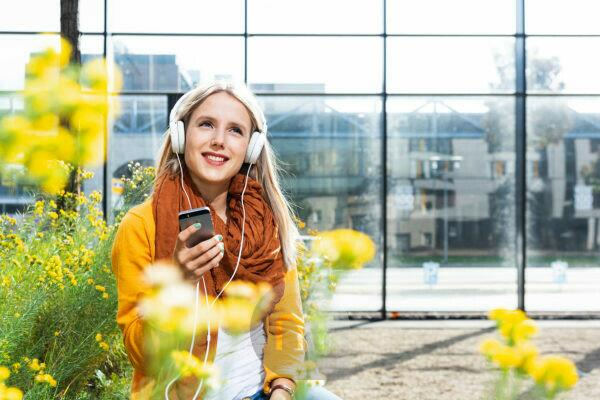 Young woman with Smartphone and earphones in front of office building, portrait