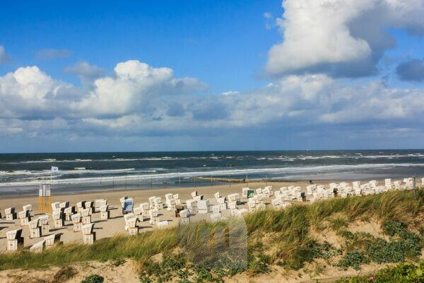 Clouds, beach chairs and waves on the beach of the island Wangerooge,