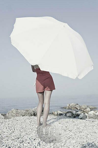 Corfu, girl on the beach with beach umbrella