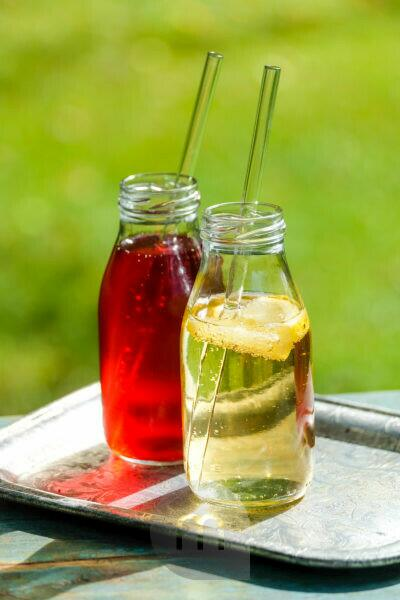 Two small glass bottles with homemade lemon and elderberry lemonade on a garden table