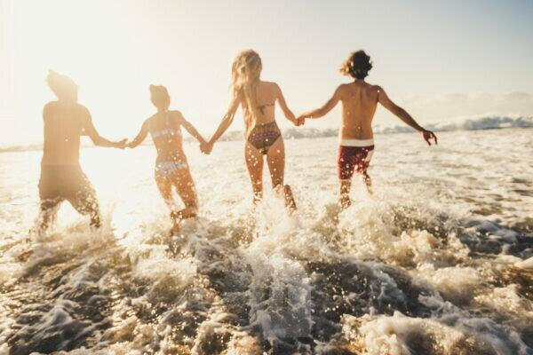 Defocused for active and motion concept people have fun running in the sea water during summer vacation - group friends together enjoy happiness - action caucasian men and women in friendship