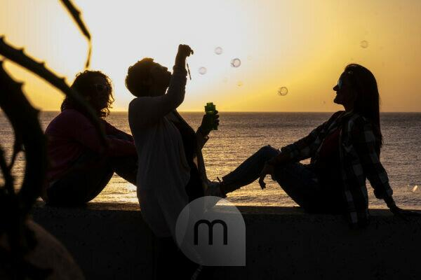 Friendship for women during the sunset - emotion and feeling with golden colors and three ladies in silhouette playing with bubbles soap - vacation and outdoor leisure activity concept