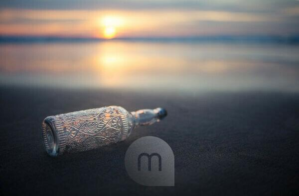 Glasflasche mit Verzierungen am Strand in abendlichem Licht