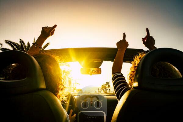 People happy for travel vacation with convertible car giving up hands and dancing for the sea summer holiday vacation - sun on the horizon and joyful concept for free women friends together