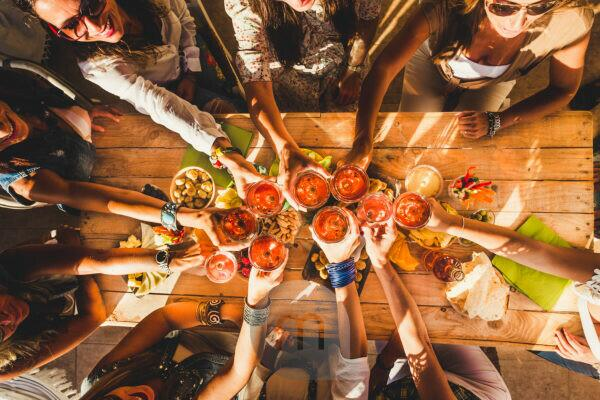 Above view group of friends people enjoy food and drinks toasting and clinking with red wine glasses all together having. fun - celebration and friendship concept - coloured background