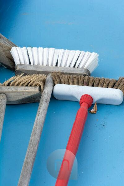 Brooms are lying on a blue floor