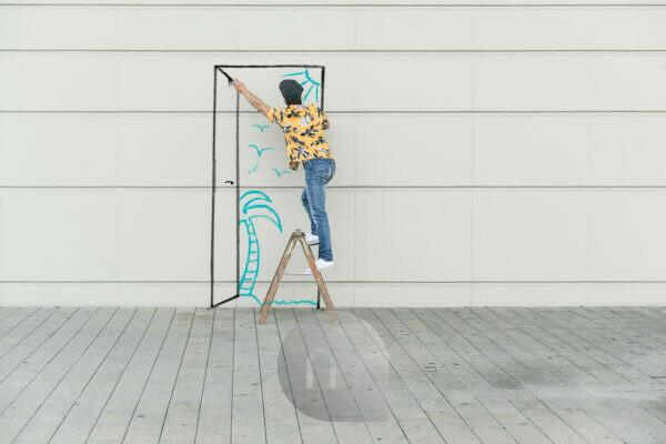 Digital composite of young man drawing a beach at a wall