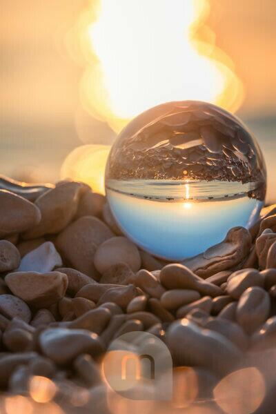 crystal ball on the pebble beach of Mošćenička Draga at sunrise, Primorje-Gorski Kotar County, Croatia
