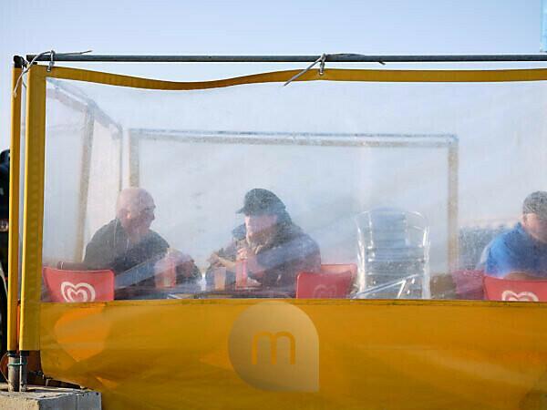 Zwei Fischer am Abend in einem Imbiss hinter einem Windschutz im Hafen von Roscoff in der Bretagne.