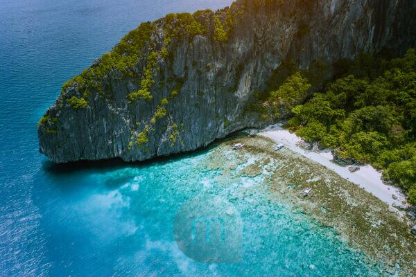 Aerial drone view of tropical beach with banca boats on Entalula Island. Karst limestone rocky mountains surrouns blue bay with beautiful coral reef.