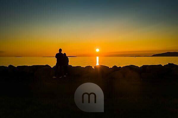 Couple enjoying the sunset, Saebraut street, Reykjavik, Iceland