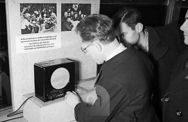 """Visitors walking through the exhibition of the """"Sonderfahrt der deutschen Technik"""" propaganda exhibition, here the Volksempfänger radio, Germany 1930s."""