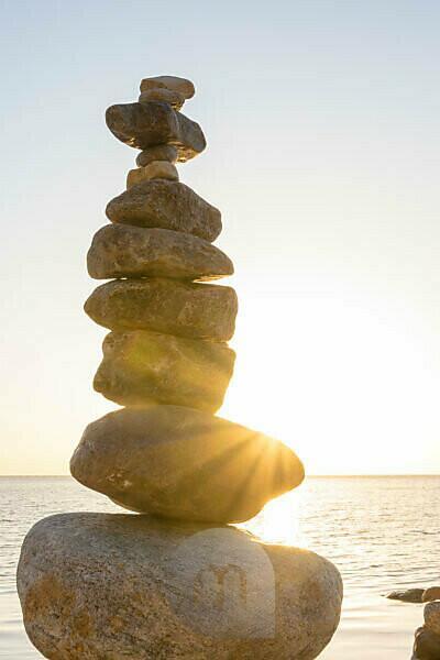 Ostsee, Rügen, Steinmännchen im Gegenlicht mit Sonnenstrahlen, Morgenstimmung