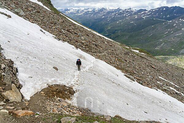 Europa, Österreich, Tirol, Ötztaler Alpen, Ötztal, Obergurgl, Bergwanderer überquert ein Altschneefeld im Aufstieg zum Ramolhaus