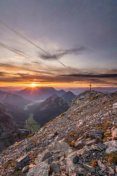 Sonnenaufgang über dem Achensee hinter dem Gipfelkreuz des Sonnjoch im Karwendel.