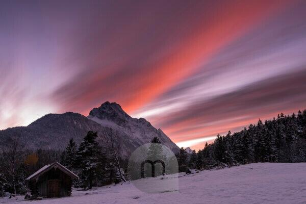 Red sunset on the Wetterstein. Long exposure of a mountain hut and the Wetterstein Mountains above after sunset. Recorded at Mittenwald. The colors are reflected by the snow