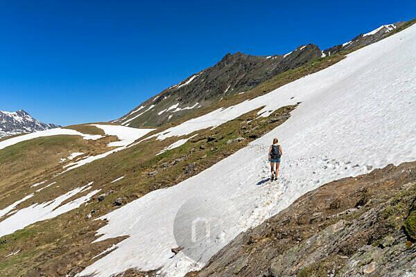 Europa, Österreich, Tirol, Ötztaler Alpen, Ötztal, Wanderin überquert ein Altschneefeld im Rotmoostal bei Obergurgl