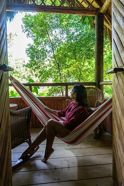 Amerika, Karibik, Große Antillen, Dominikanische Republik, Cabarete, Frau sitzt in der Hängematte auf dem Balkon ihres Bungalows im Natura Cabana Boutique Hotel & Spa