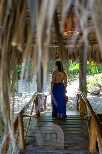 America, Caribbean, Greater Antilles, Dominican Republic, Cabarete, woman stands on a small wooden bridge in the Natura Cabana Boutique Hotel & Spa