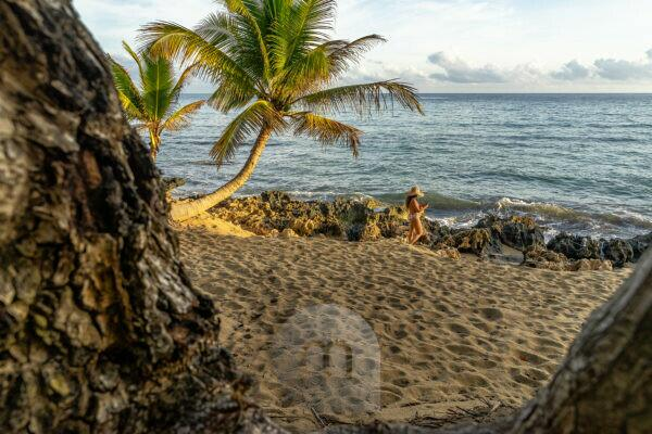 America, Caribbean, Greater Antilles, Dominican Republic, Cabarete, woman strolls on the beach of the Natura Cabana Boutique Hotel & Spa