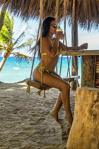 Amerika, Karibik, Große Antillen, Dominikanische Republik, Cabarete, Frau sitzt auf einer Schaukel an der Strandbar und trinkt einen Cocktail im Natura Cabana Boutique Hotel & Spa