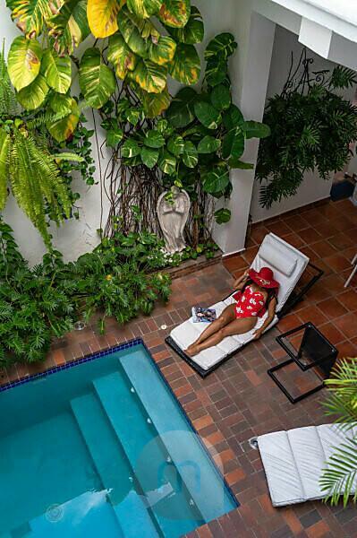 Amerika, Karibik, Große Antillen, Dominikanische Republik, Santo Domingo, Zona Colonial, Hotel Colonial 154 H Boutique, Frau mit Sonnenhut auf einer Sonnenliege am Pool