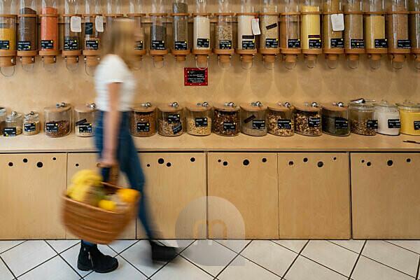 Eine junge Kundin geht an einem Regal mit Abfüllbehältern für Getreide vorbei, Detail aus einem Unverpacktladen.