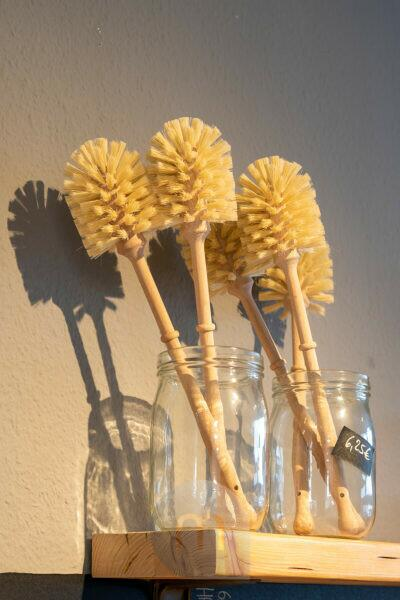 Toilet brushes are in glasses in an unpacked shop.